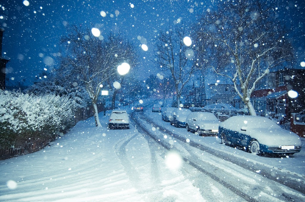 A street covered in snow, with snow still falling