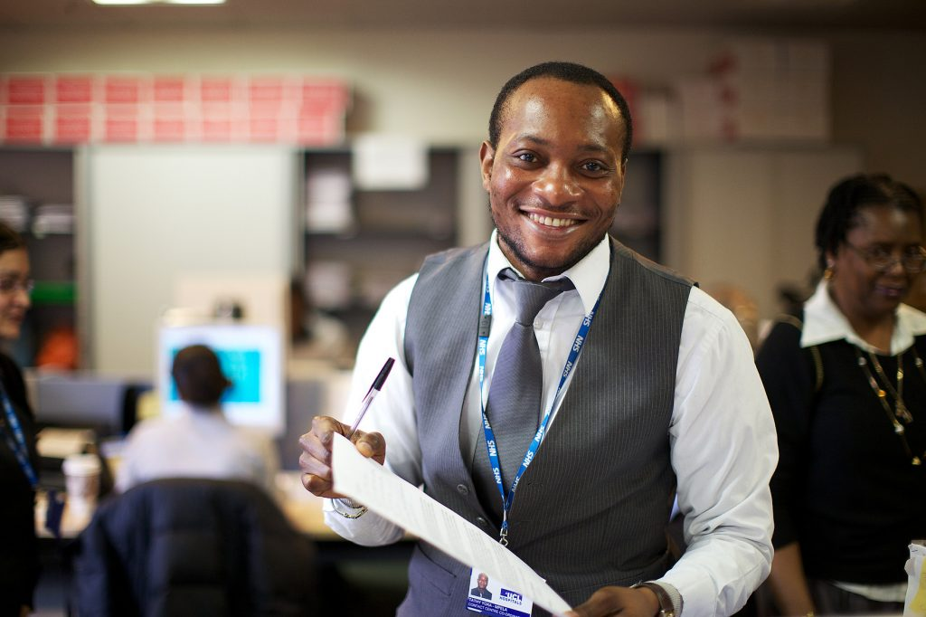 Unique ID: NHS_UCLH_DAY 1 CALL CENTRE_0045  Caption: Hospital administration, office, call centre. A member of staff looking at the camera, smiling, holding paperwork. People working in background.  Restrictions:   Copyright: ©
