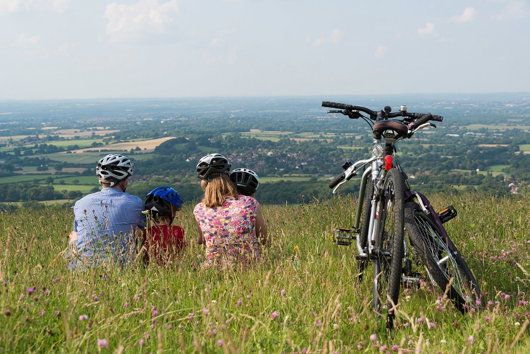 Family sat on hill at Ditchling Beacon overlooking the South Downs. Bicycles to the side of them.