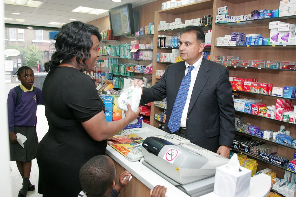 Unique ID: 9441  Caption: A pharmacy or dispensing chemist counter. A pharmacist behind the counter talking to and serving a woman. High street pharmacy.   Restrictions:   Copyright: ©Crown Copyright