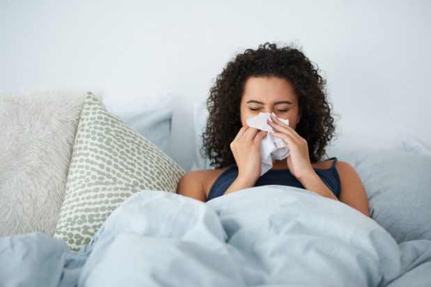 A woman sitting in bed under a duvet blowing her nose