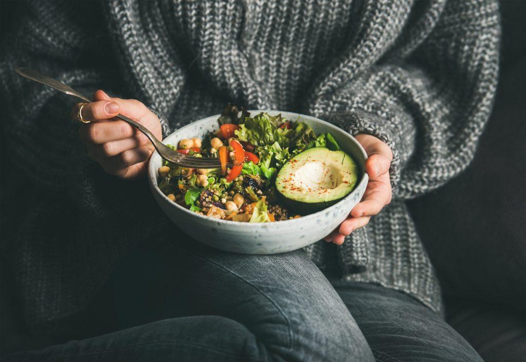 Women holding a bowl of vegetarian dinner.