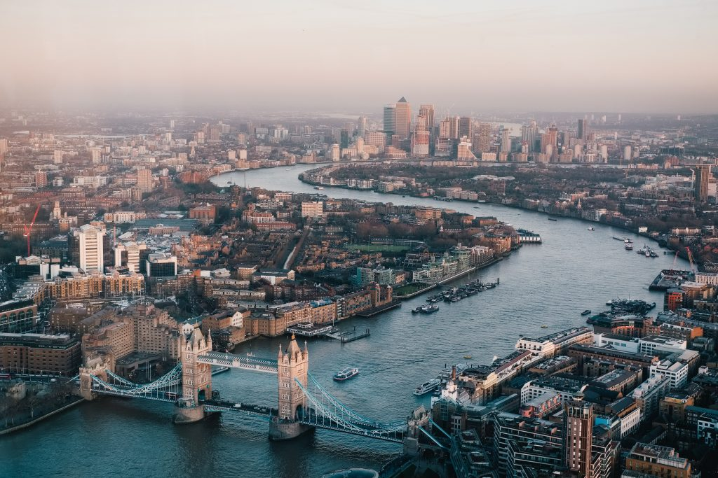 Ariel shot of London showing the River Thames, Tower Bridge and in the background Canary Wharf.