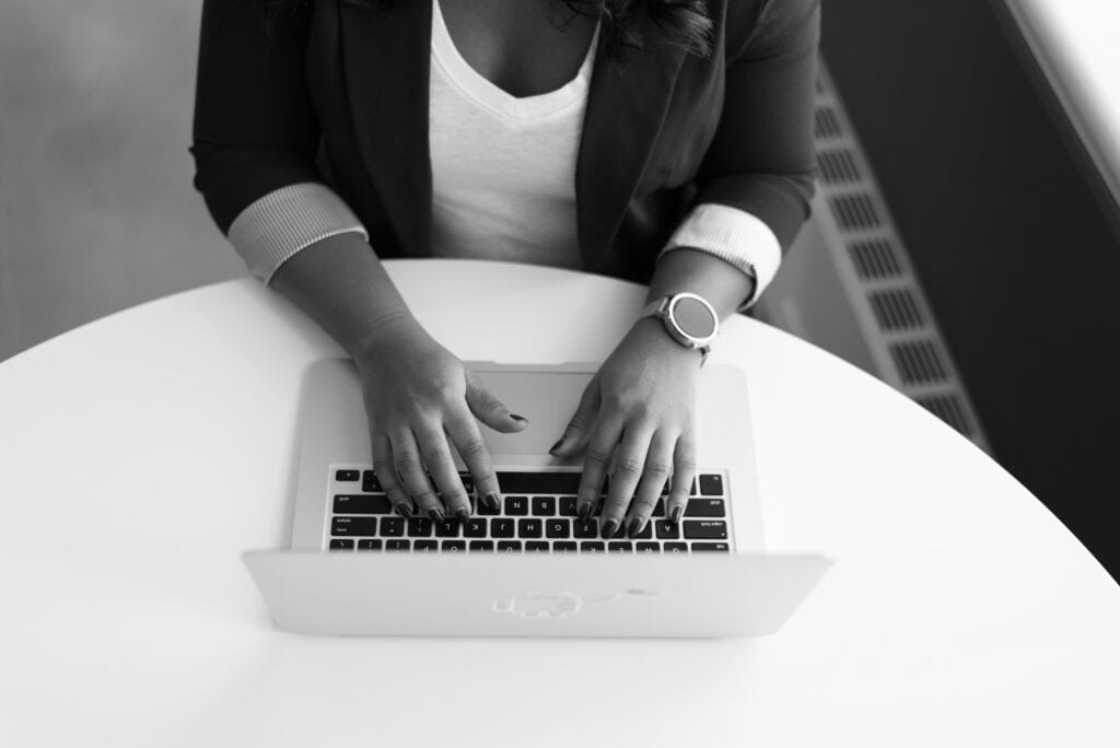 Person sitting a table with laptop, hands and arms in view